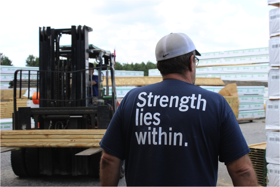 "Man looking at a forklift with wood wearing a shirt that says ""strength lies within"""