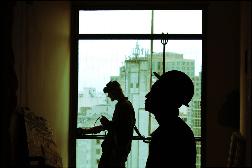 Silhouette of two men inside of a building being built