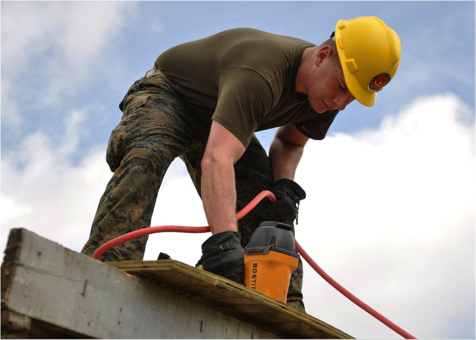 Man with a power tool into a roof with a hardhat on