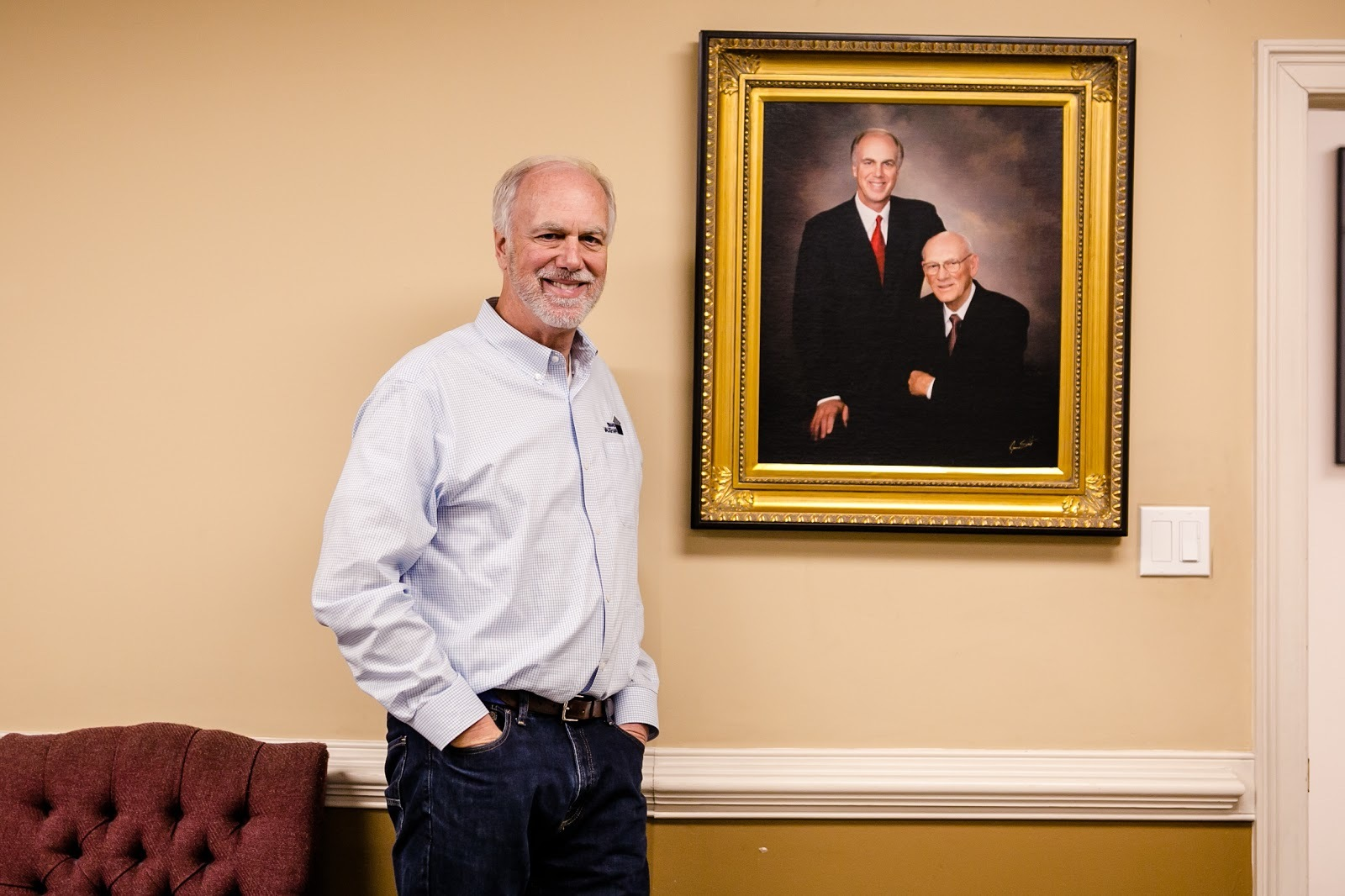 Chip stands in front of picture of him and Jon.