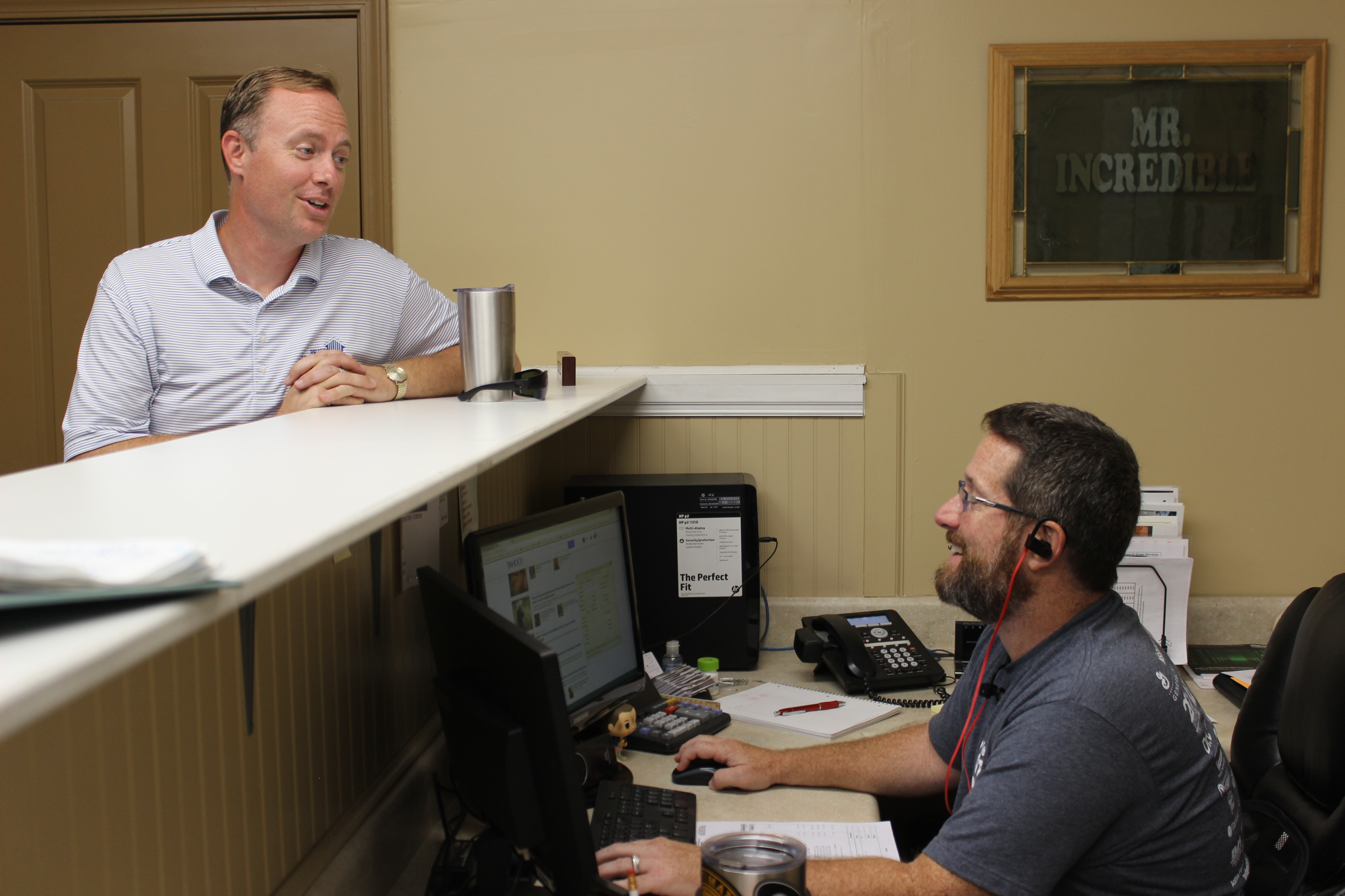 Two men talking over a desk to each other