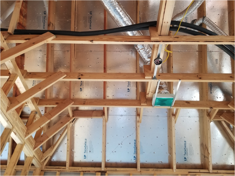 View of the inside structure of the framed house with the insulation on one side.
