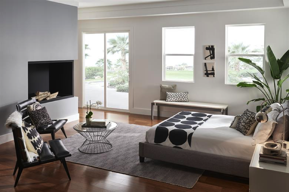 Bedroom with many windows and a modern fireplace that is bordered with black. There is a large bed with two chairs and a seating area. The hardwood floors have a tan rug on top of it. There are three large windows