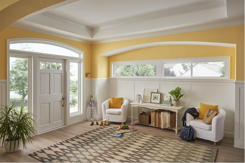 A large room with yellow walls and white detailing. There is a tray ceiling that is detailed white. A tan and black rug with two white armchairs and yellow pillows. There is a large door