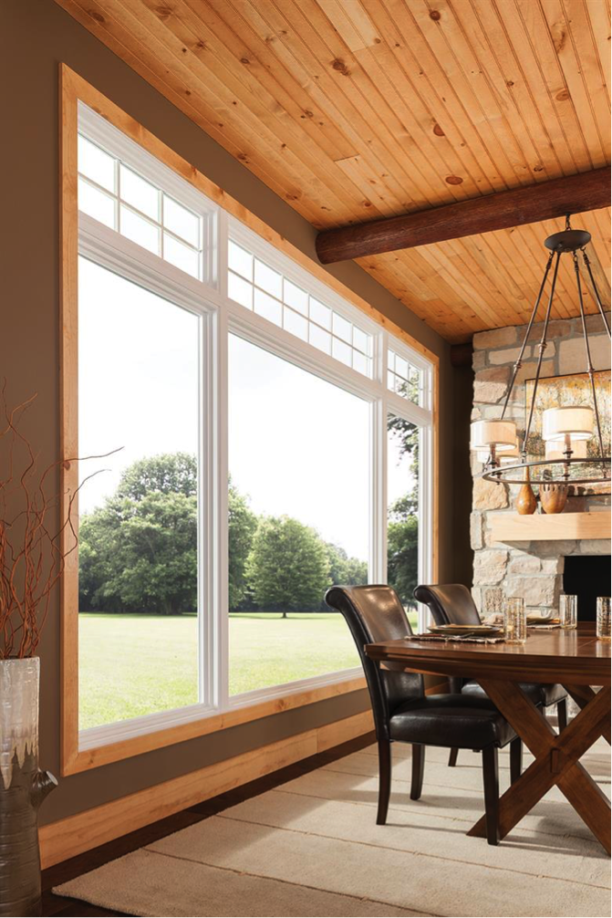 Image of a dining room with large farm windows. There is wood shiplap detailing on the roof. A wooden table that cris crosses at the bottom is in the image as well.