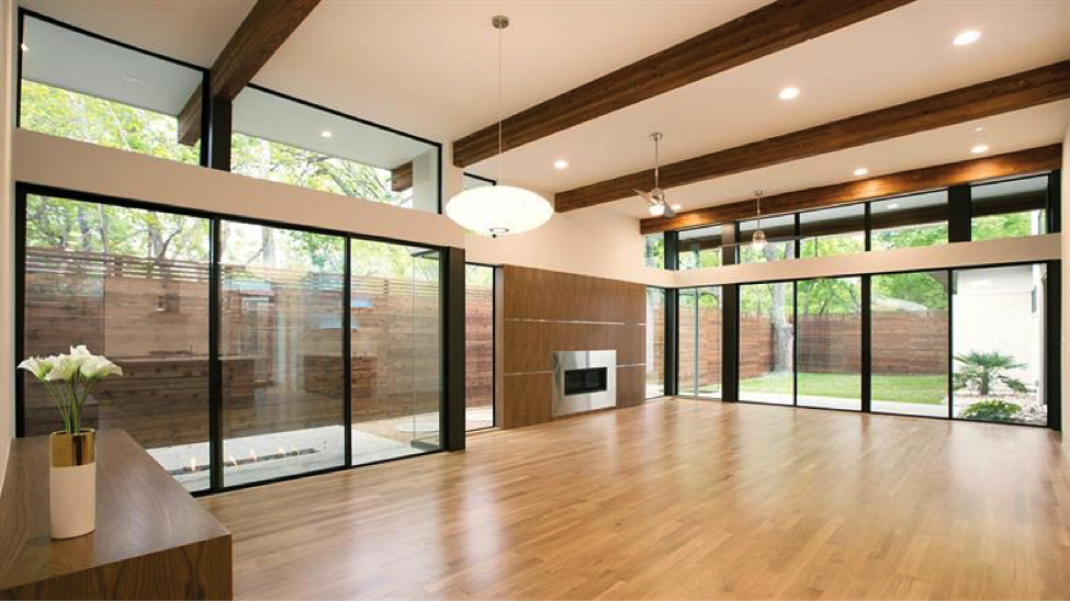 A large room with many big windows and a light hardwood flooring. The roof has five wood beams with hanging lighting.