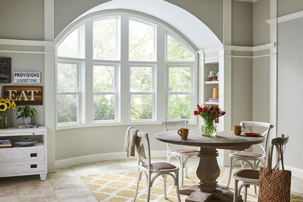 A tea room with an arch of four windows with a small table that has flowers on it. There is a white hutch to the left that has a sign that says EAT. The main focus is the arch way window.