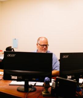 Chris Ketchum sits at his desk looking at monitors