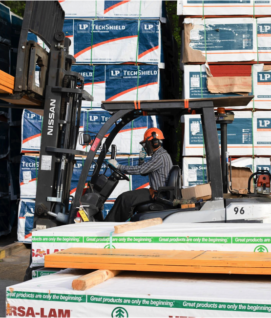 Image of man stacking siding with a forklift.