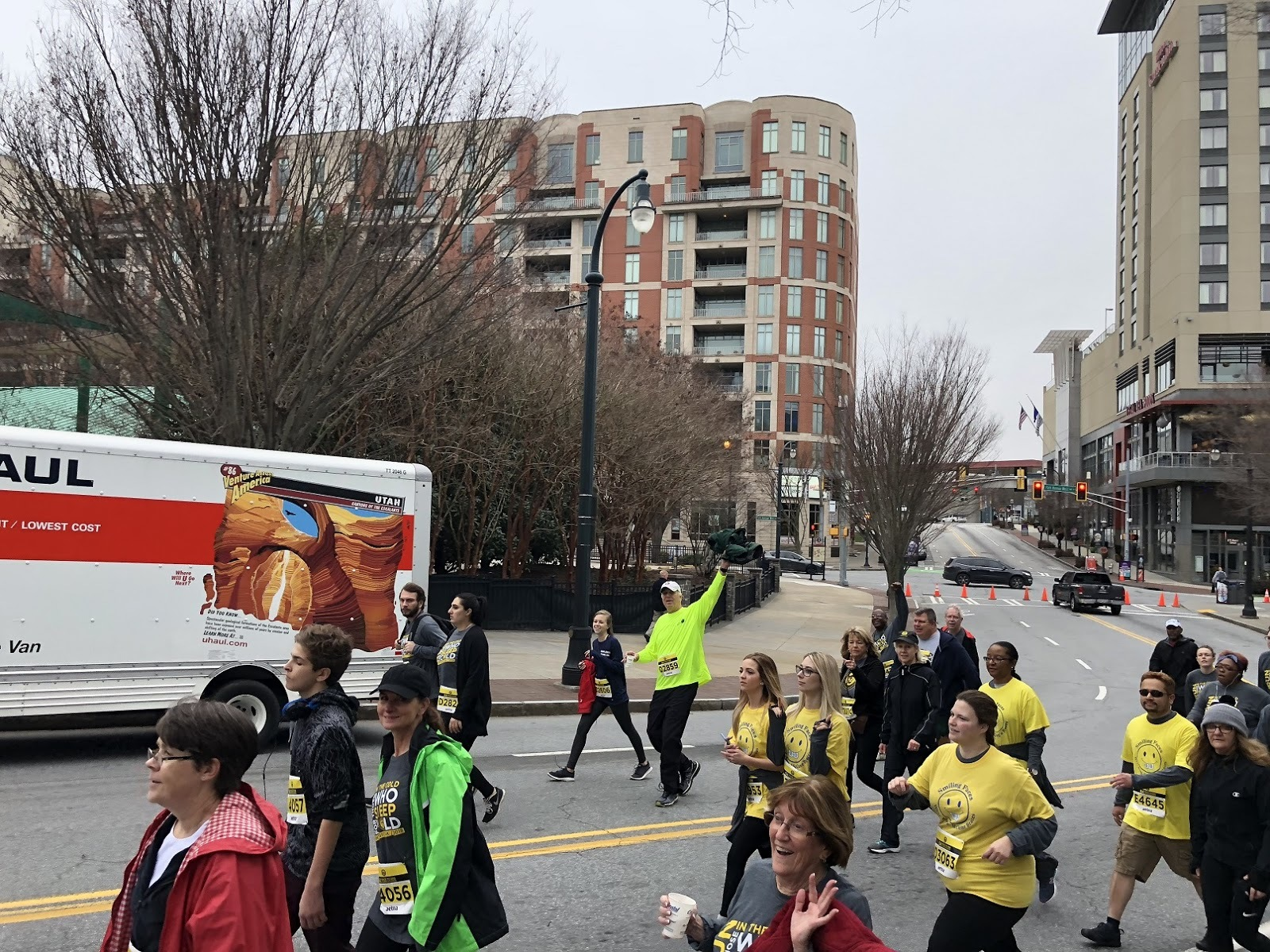 Candid image of a charity run with people running in different colored shirts in the street