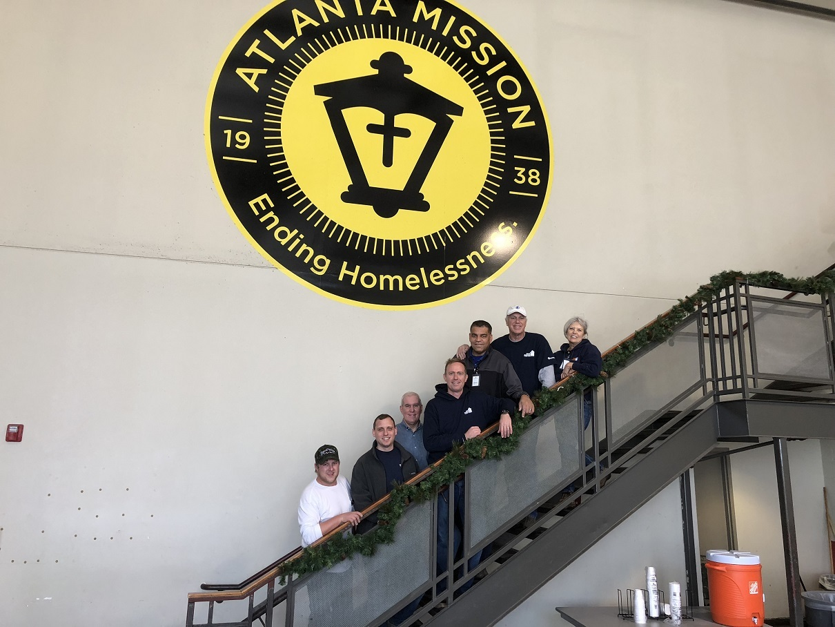 Image of people posing along a staircase in from of an Atlanta Mission: Ending Homelessness sign