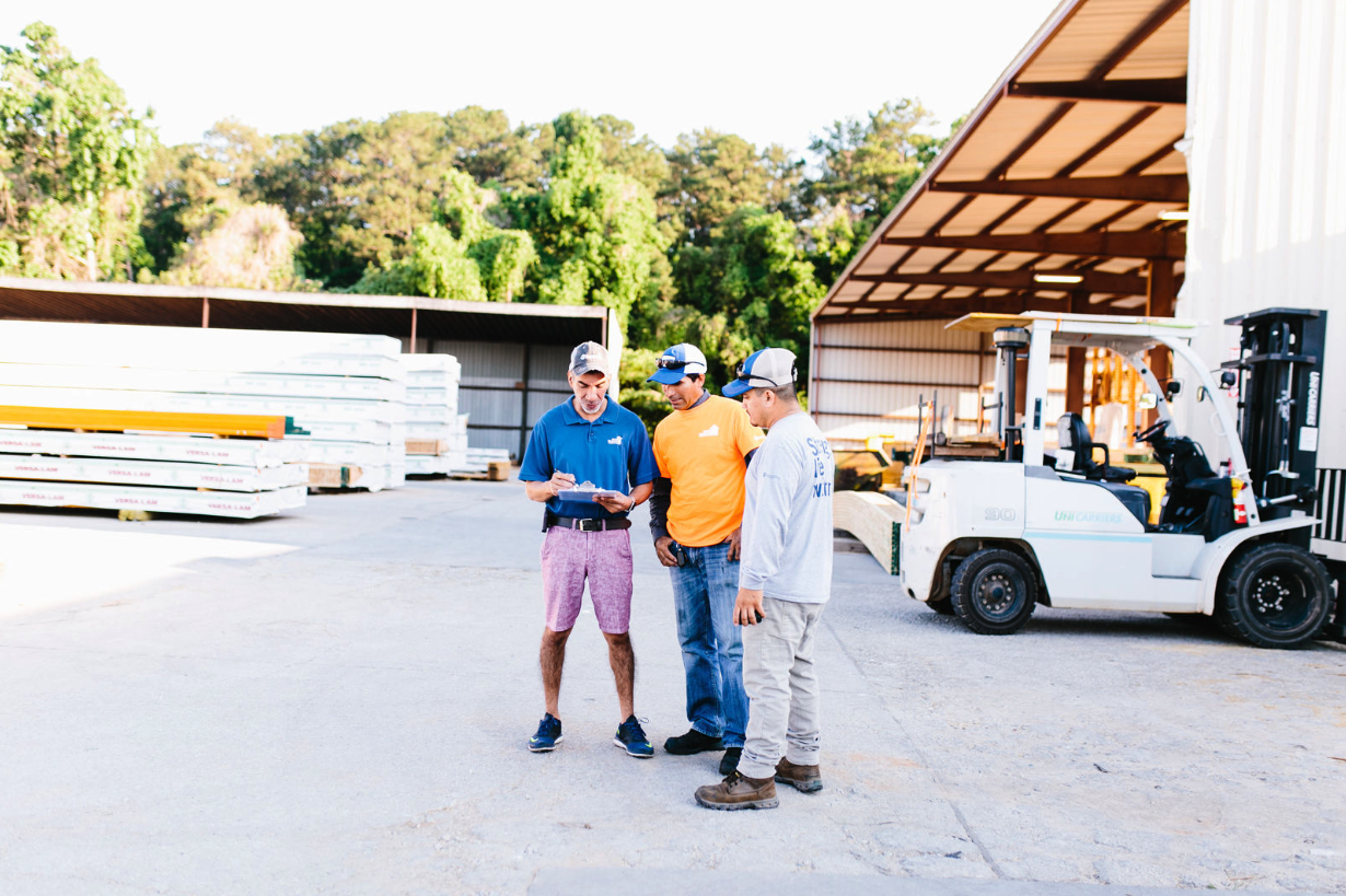 Three men on a construction site discussing.