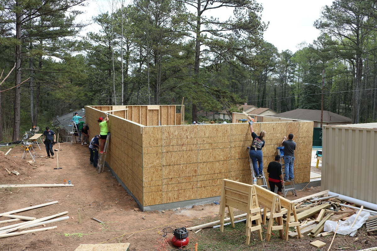 Image of a house being built in the woods for charity.