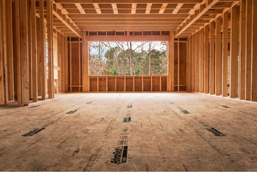 Inside of uncompleted house showcasing the framing as well as a large window that has been framed out.