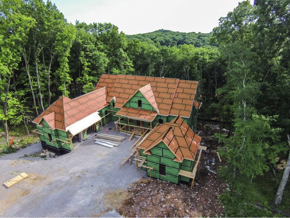 Aerial view of a large uncompleted home in the woods with siding exposed.
