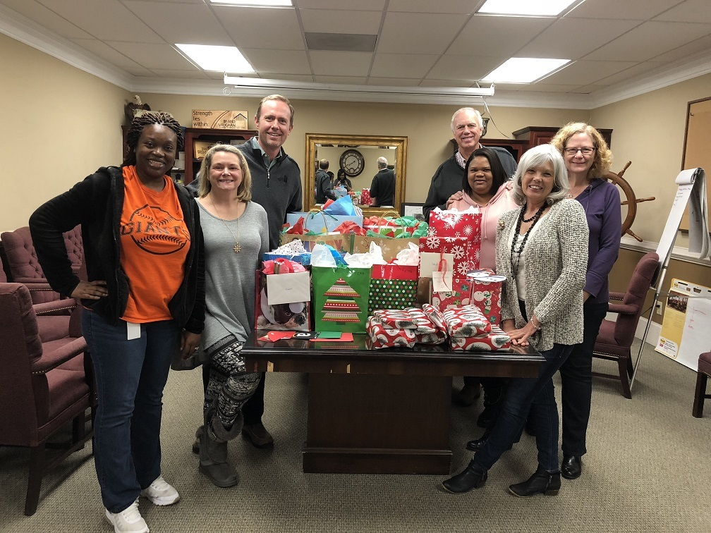 A group poses around a table of gifts at a philanthropy event.
