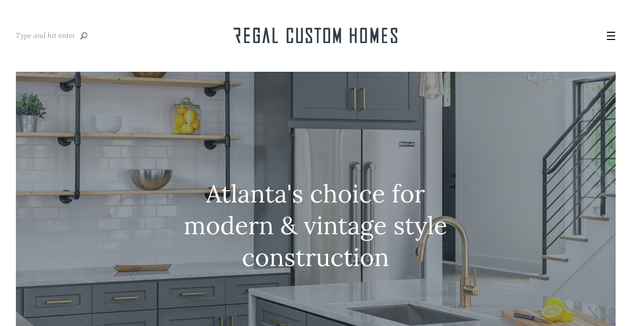 Regal custom homes website with their motto spread across a slightly blurry picture of a white and blue kitchen with exposed cabinets