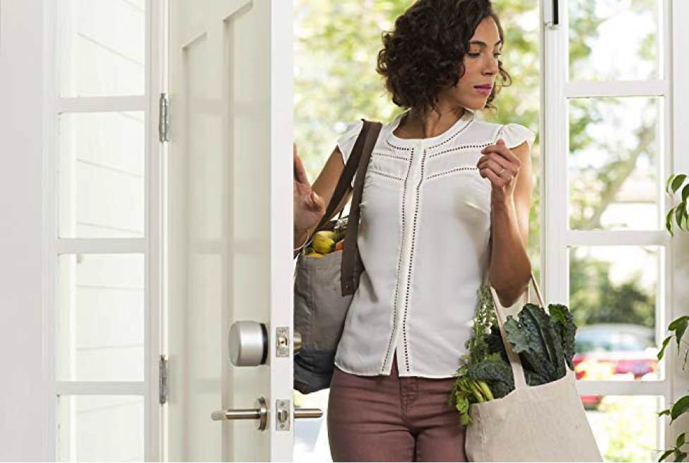 Image of a woman walking through a white door with a grocery bag full of leafy greens.