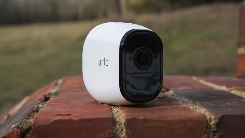 Arlo device. it is placed on a brick stair and the device is white and the area around the camera is black