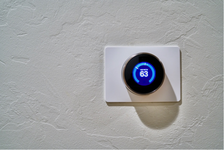 Nest thermostat on the wall of a home. The thermostat is digital with blue and white writing.