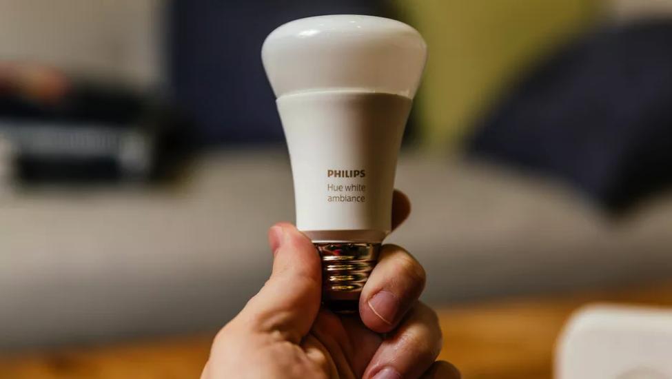 Smart Phillips lightbulb that is being held.