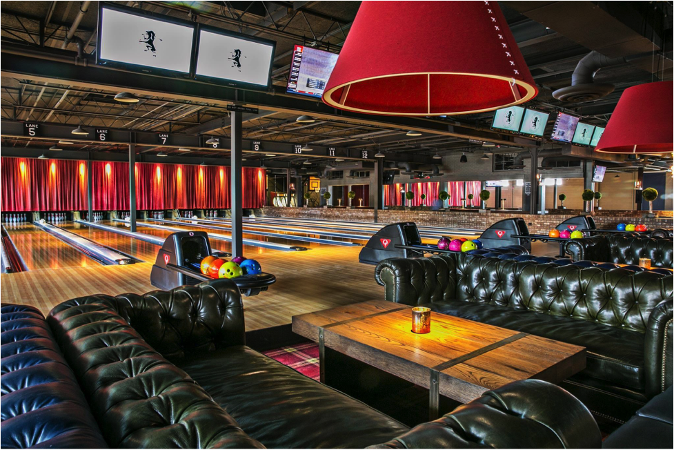 Image of a bowling alley with large sectional couches and bright lights.