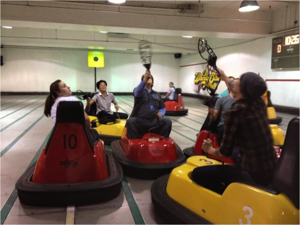 People laughing and having fun while riding bumper cars.