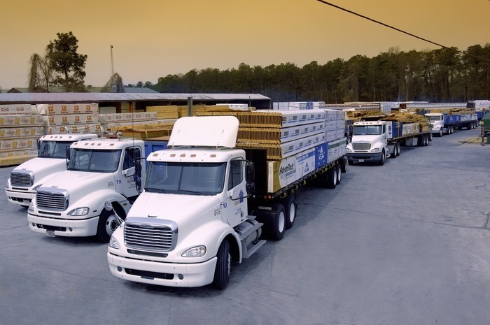 Many tractor trailers line up next to each other with lumber in the back.