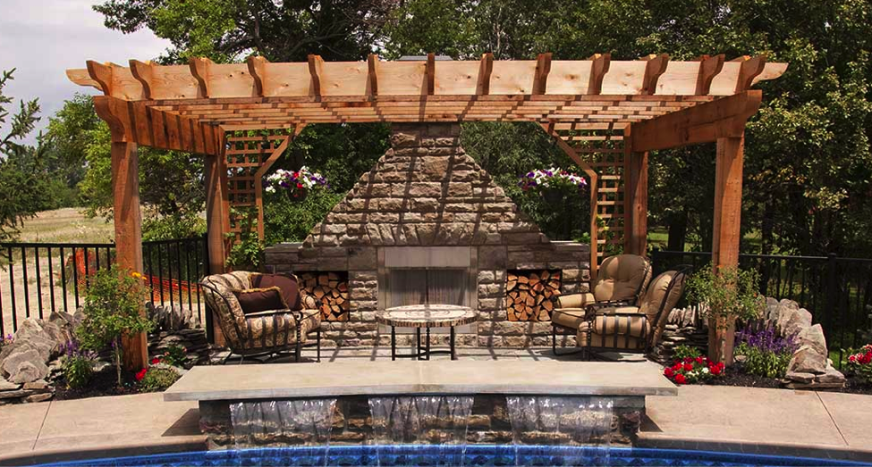 An outdoor living space with a fireplace as well as a wooden cover. There is a pool waterfall